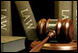 Image of law books behind a gavel that is used in the courtroom.